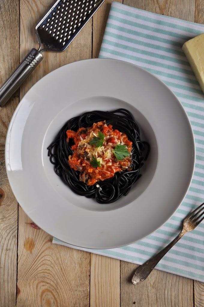 Czarny makaron ze ślimakami i anchois w sosie pomidorowym z serem cheddar
