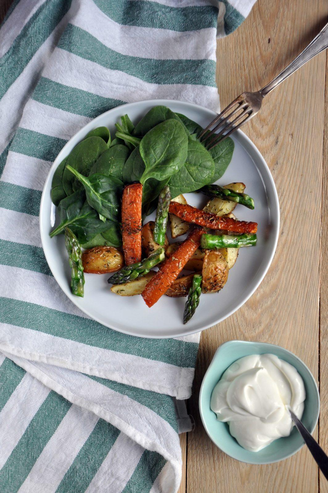 Pieczone warzywa: młode ziemniaki i marchewka podane ze szparagami, świeżym szpinakiem i kwaśną śmietaną